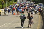 FILE - In this Oct. 12, 2019, file photo, migrants walk down Highway 200 en route to Huixtla, near Tapachula, Chiapas state, Mexico. Five American journalists brought a lawsuit Wednesday, Nov. 20, 2019, against the U.S. government that alleges border authorities violated their First Amendment rights by inspecting their cameras and notebooks and questioning them extensively about their coverage of last year's migrant caravan.  (AP Photo/Isabel Mateos, File)