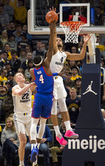 DePaul forward Paul Reed, center, goes up for a basket against Marquette forward Theo John, right, during the first half of an NCAA college basketball game, Wednesday, Jan. 23, 2019, in Milwaukee. (AP Photo/Darren Hauck)