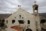 FILE - This May 18, 2017 file photo, shows a Syrian flag raised over the damaged Saint Mary Roman Orthodox church at the mountain resort town of Zabadani in the Damascus countryside, Syria. The Qatar-based Syrian Network for Human Rights, a Syrian war monitor associated with the opposition said in its report Monday, Sept. 9, 2019, that over 120 Christian places of worship have been damaged or destroyed by all sides in the country's eight-year conflict. (AP Photo/Hassan Ammar, File)