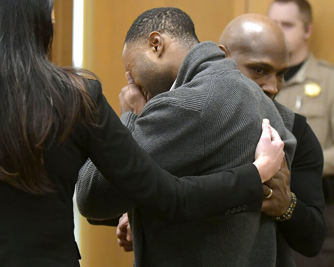Torrey Green cries while being consoled by defense attorney Skye Lazaro, left, and private investigator E. Christian Warmsley as a jury finds him guilty of eight charges including five counts of rape and a charge sexual battery in connection to reports from six women accusing him of sexual assault while he was a football player at Utah State University, Friday, Jan.18, 2019 in Brigham City, Utah. (Eli Lucero/Herald Journal via AP, Pool)