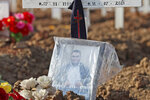 A photograph is placed on the grave of a man who died of COVID-19 at Rorotan Cemetery in Jakarta, Indonesia, Wednesday, Sept. 1, 2021. Family members left tokens of remembrance on the graves of their loved loved ones that will help future visitors find the grave in the sea of those buried at the cemetery which was reserved for those who died of coronavirus. (AP Photo/Achmad Ibrahim)