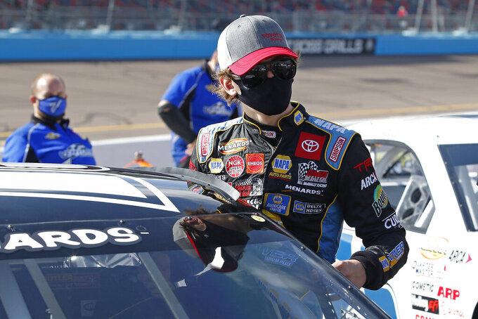 Jesse Love climbs into his race car on pit road prior to the ARCA Series auto race at Phoenix Raceway, Saturday, Nov. 7, 2020, in Avondale, Ariz. (AP Photo/Ralph Freso)