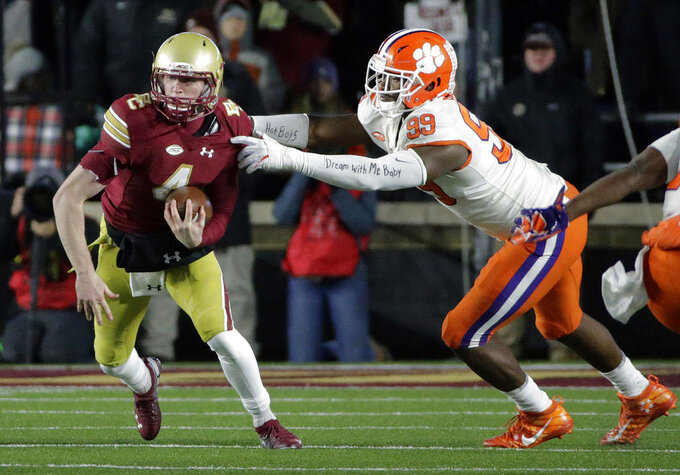 Boston College back-up quarterback EJ Perry, left, tries to get away from Clemson defensive end Clelin Ferrell during the first half of an NCAA college football game, Saturday, Nov. 10, 2018, in Boston. (AP Photo/Elise Amendola)