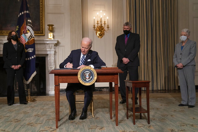 President Joe Biden signs a series of executive orders on climate change, in the State Dining Room of the White House, Wednesday, Jan. 27, 2021, in Washington. From left, Vice President Kamala Harris, Biden, White House science adviser Dr. Eric Lander, and National Climate Adviser Gina McCarthy. (AP Photo/Evan Vucci)