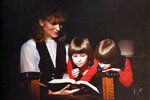 This image provided by Coral Theill, shows Theill with her twin girls in 1984, reading from their family Bible. (Coral Theill via AP)