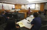 Yadira Santos, center, a victim of the Champlain Towers South collapse, speaks to Judge Michael Hanzman about her wishes for the site, during a hearing Wednesday, July 21, 2021, in Miami. Hanzman said victims and families who suffered losses in the collapse of the 12-story oceanfront Florida condominium will get a minimum of $150 million in compensation initially. (Carl Juste/Miami Herald via AP, Pool)