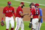 Texas Rangers' Ronald Guzman, left, and Sam Huff (74) watch as Luis Garcia, second from left, turns the ball over to manager Chris Woodward after giving up a grand slam to the Oakland Athletics during the first inning of a baseball game in Arlington, Texas, Friday, Sept. 11, 2020. (AP Photo/Tony Gutierrez)