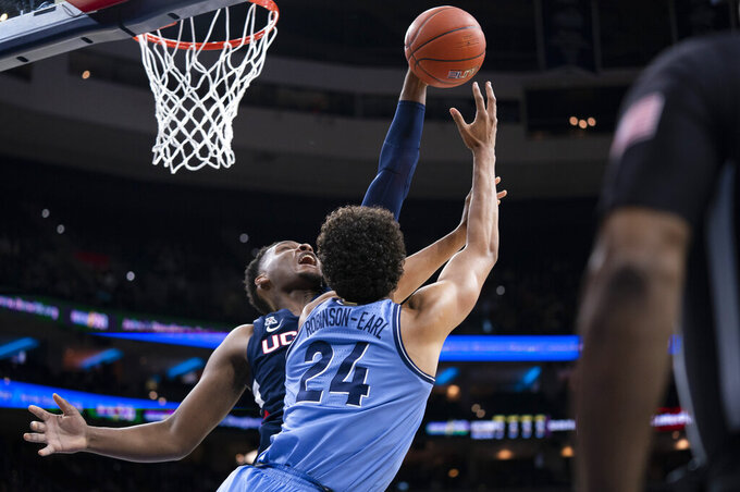 Connecticut's Josh Carlton, left, blocks the shot attempt by Villanova's Jeremiah Robinson-Earl, right, during the first half of an NCAA college basketball game Saturday, Jan. 18, 2020, in Philadelphia. (AP Photo/Chris Szagola)