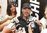 Jimmie Johnson, center, talks with reporters during a NASCAR auto race news conference at Daytona International Speedway, Friday, July 5, 2019, in Daytona Beach, Fla. (AP Photo/Terry Renna)