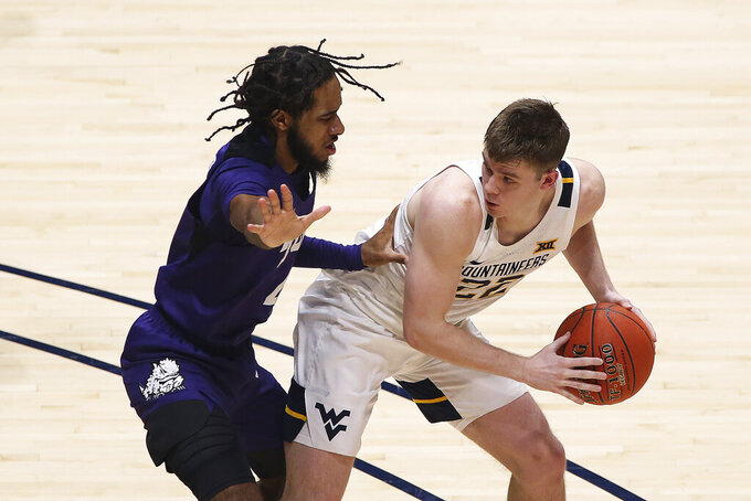 West Virginia guard Sean McNeil (22) is defended by TCU guard PJ Fuller (4) during the first half of an NCAA college basketball game Thursday, March 4, 2021, in Morgantown, W.Va. (AP Photo/Kathleen Batten)