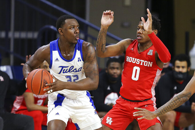 Tulsa's Austin Richie is defended by Houston's Marcus Sasser during the first half of an NCAA college basketball game in Tulsa, Okla., Tuesday, Dec. 29, 2020. Tulsa won 65-64. (AP Photo/Dave Crenshaw)