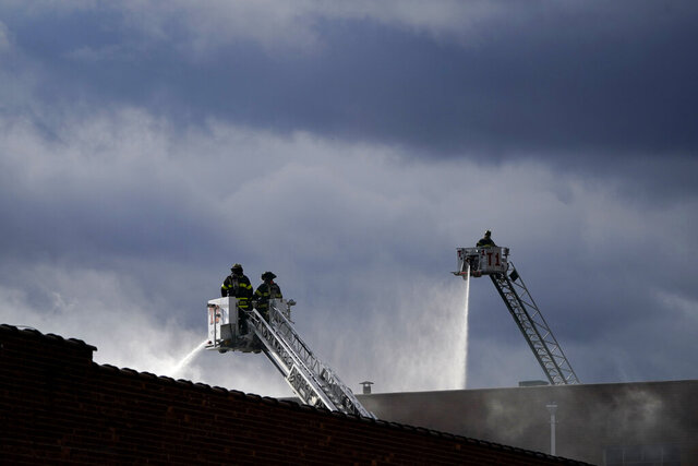 Firefighters work at the scene of a building fire in Englewood, N.J., Wednesday, Dec. 2, 2020. Firefighters from several towns battled the blaze in a commercial building. (AP Photo/Seth Wenig)