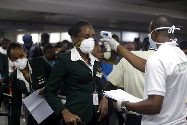 FILE - In this Wednesday, March 4, 2020 file photo, a Nigerian port health official, right, uses a thermometer to screen Ethiopian Airline cabin crews for the coronavirus, upon arrival at the Murtala Muhammed International Airport in Lagos, Nigeria. Questions are swirling in Africa and elsewhere over the financial wisdom of sustaining prestige carriers that have a tiny share of an aviation market that sees no recovery in sight as sub-Saharan Africa faces its first recession in a quarter-century amid coronavirus-related travel restrictions. (AP Photo/Sunday Alamba, File)
