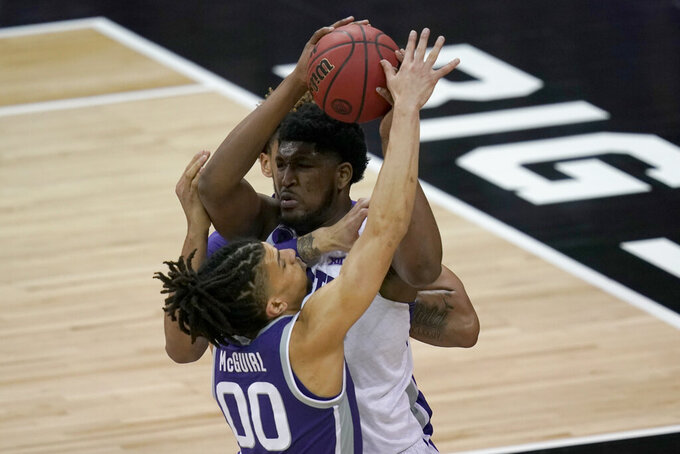 TCU center Kevin Samuel is covered by Kansas State guard Mike McGuirl (00) during the first half of an NCAA college basketball game in the first round of the Big 12 men's tournament in Kansas City, Mo., Wednesday, March 10, 2021. (AP Photo/Orlin Wagner)