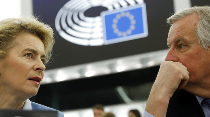 European Commission President Ursula von der Leyen, left, talks to to European Union chief Brexit negotiator Michel Barnier during a debate on a proposed mandate for negotiations for a new partnership with the United Kingdom of Great Britain and Northern Ireland, at the European Parliament in Strasbourg, eastern France, Tuesday, Feb.11, 2020. (AP Photo/Jean-Francois Badias)