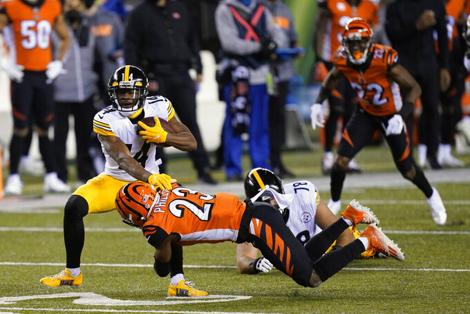 Pittsburgh Steelers' Ray-Ray McCloud (14) is tackled by Cincinnati Bengals' Darius Phillips (23) during the first half of an NFL football game, Monday, Dec. 21, 2020, in Cincinnati. (AP Photo/Bryan Woolston)