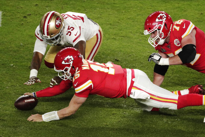 Kansas City Chiefs quarterback Patrick Mahomes (15) and San Francisco 49ers' Dee Ford (55), go after a loose ball after it was knocked out of his Mahomes' hands during the second half of the NFL Super Bowl 54 football game Sunday, Feb. 2, 2020, in Miami Gardens, Fla. To the right is Kansas City Chiefs' Eric Fisher (72). (AP Photo/Charlie Riedel)