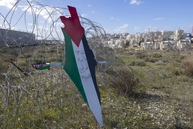 Protesters post a placard with the colors of the Palestinian flags and Arabic that reads