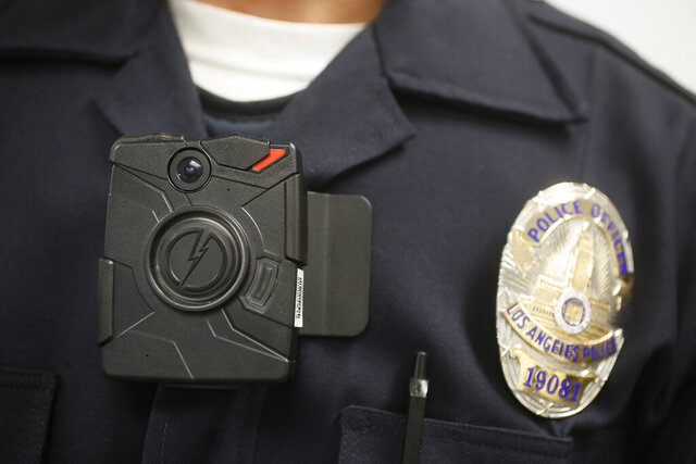 FILE - This Jan. 15, 2014 file photo shows a Los Angeles Police officer wearing an on-body cameras during a demonstration for media in Los Angeles. Governments must bear the costs of redacting police body camera video before making it public, the California Supreme Court ruled Thursday, May 28, 2020, in a decision that was hailed by media organizations but will be costly for cities and counties. (AP Photo/Damian Dovarganes,File)