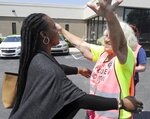 FILE - In this May 17, 2019 file photo, Dr. Yashica Robinson, is greeted with a hug from Josie Poland, a clinic escort, while arriving for work at the Alabama Women's Wellness Center in Huntsville, Ala. Abortion providers are asking a federal judge to block an Alabama law that would ban most abortions in the state. The American Civil Liberties Union and Planned Parenthood filed the lawsuit Friday, May 24 on behalf of Alabama abortion providers seeking to overturn the nation's most stringent abortion law. The plaintiffs in the case are the three Alabama clinics that perform abortions, Planned Parenthood and Robinson, an obstetrician who also provides abortions at the Huntsville clinic.  (AP Photo/Eric Schultz, File)