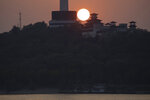 The sun sets over the television tower along the Yangtze River in Wuhan in central China's Hubei province on Wednesday, April 8, 2020. Streets in the city of 11 million people were clogged with traffic and long lines formed at the airport, train and bus stations as thousands streamed out of the city to return to homes and jobs elsewhere. Yellow barriers that had blocked off some streets were gone, although the gates to residential compounds remained guarded. (AP Photo/Ng Han Guan)
