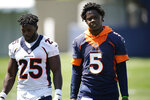 Denver Broncos running back Melvin Gordon, left, chats with quarterback Teddy Bridgewater after taking part in drills at NFL football training camp, Wednesday, July 28, 2021, in Englewood, Colo. (AP Photo/David Zalubowski)
