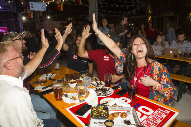 Dana Sherrod, right, celebrates with fellow Republicans while watching Election Day results on television during the Republican watch party at Krause's Cafe in New Braunfels, Texas, on Tuesday, Nov. 3, 2020. Trump has won Texas by the thinnest margin of any Republican in decades. (Mikala Compton/Herald-Zeitung via AP)