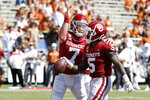 Oklahoma quarterback Spencer Rattler (7) congratulates running back T.J. Pledger (5) after Pledger scored against Texas during the second half of an NCAA college football game in Dallas, Saturday, Oct. 10, 2020. Oklahoma defeated Texas 53-45 in four overtimes. (AP Photo/Michael Ainsworth)