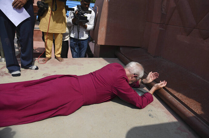 The Archbishop of Canterbury Rev. Justin Welby, prostrates as he pays respect at the Jallianwala Bagh memorial in Amritsar, India, Tuesday, Sept. 10, 2019. More than 300 Indians attending a peaceful rally calling for independence were killed during a massacre by British colonial troops at this spot 100 years ago. (AP Photo/Prabhjot Gill)