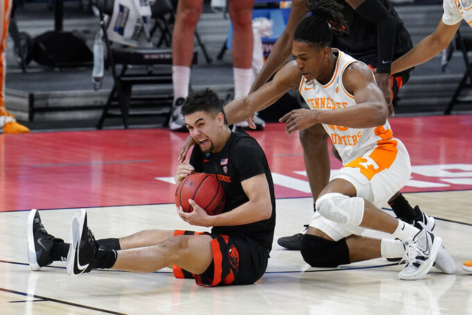 Oregon State guard Jarod Lucas (2) holds a loose ball as Tennessee guard Yves Pons (35) applies pressure during the second half of a men's college basketball game in the first round of the NCAA tournament at Bankers Life Fieldhouse in Indianapolis, Friday, March 19, 2021. (AP Photo/Paul Sancya)