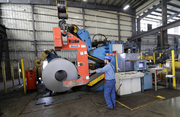 FILE- In this June 5, 2018, file photo a roll of steel is moved into position at the Borusan Mannesmann Pipe manufacturing facility in Baytown, Texas. On Friday, Sept. 14, the Federal Reserve reports on U.S. industrial production for August. (AP Photo/David J. Phillip, File)
