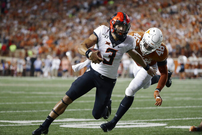 Oklahoma State quarterback Spencer Sanders (3) scrambles away from Texas linebacker Joseph Ossai (46) on a touchdown run during the first half of an NCAA college football game Saturday, Sept. 21, 2019, in Austin, Texas. (AP Photo/Eric Gay)