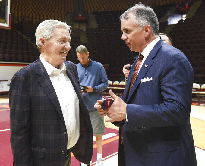New Virginia Tech men's NCAA college basketball head coach Mike Young speaks to former head football coach Frank Beamer, left, after an introductory press conference in Blacksburg, Va., Monday, April 8, 2019. (Michael Shroyer/The Roanoke Times via AP)