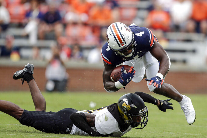Auburn running back Tank Bigsby (4) is tripped up by Alabama State Keenan Isaac (10) during the first half of an NCAA football game Saturday, Sept. 11, 2021, in Auburn, Ala. (AP Photo/Butch Dill)