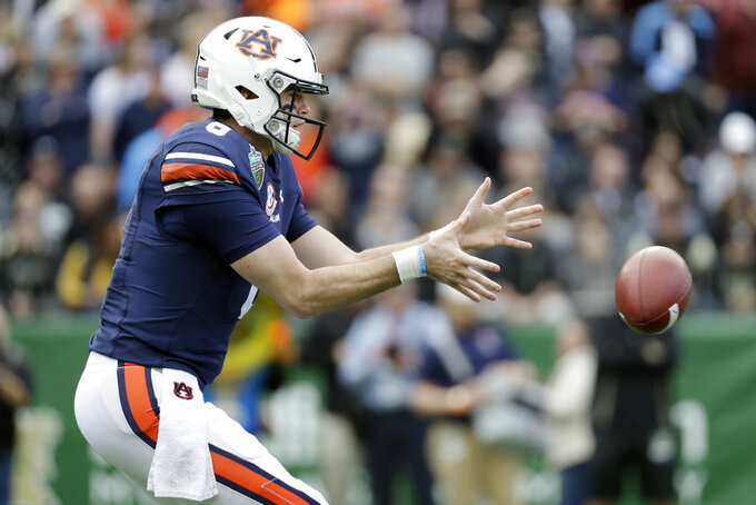 Auburn quarterback Jarrett Stidham takes a snap in the first half of the Music City Bowl NCAA college football game against Purdue Friday, Dec. 28, 2018, in Nashville, Tenn. (AP Photo/Mark Humphrey)