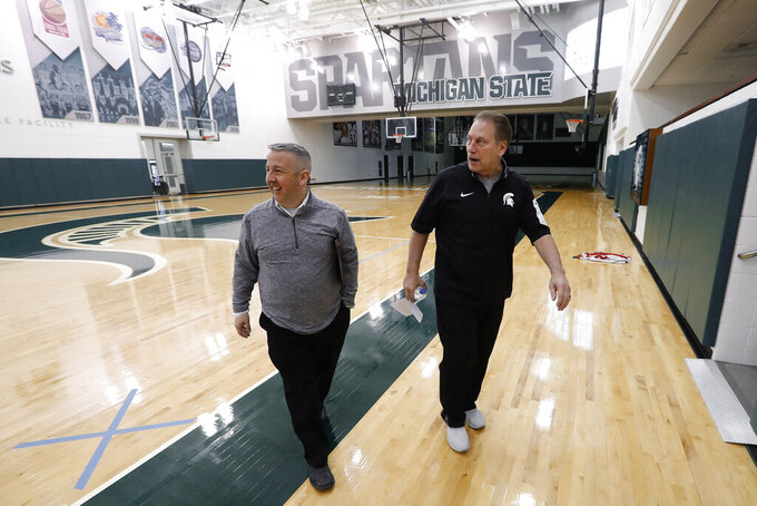 Michigan State head basketball coach Tom Izzo, right, talks with Mike Carey, Associate Director, Athletic Communications in East Lansing, Mich., Monday, Feb. 18, 2019. Izzo and Michigan coach John Beilein are friendly rivals, whose highly ranked NCAA college basketball teams will play for the first time this season on Sunday at Crisler Arena. As much as Beilein and Izzo genuinely like and respect each other, the highly competitive coaches want to win. (AP Photo/Paul Sancya)