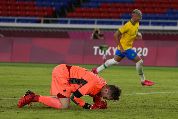Germany's goalkeeper Florian Mueller kneels after Brazil's Richarlison sacred his side's third goal during a men's soccer match at the 2020 Summer Olympics, Thursday, July 22, 2021, in Yokohama, Japan. (AP Photo/Kiichiro Sato)