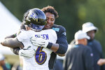 Carolina Panthers defensive end Frank Herron, right, hugs Baltimore Ravens linebacker Patrick Queen before a joint practice hosted by Carolina at the NFL football team's training camp in Spartanburg, S.C., Wednesday, Aug. 18, 2021. (AP Photo/Nell Redmond)