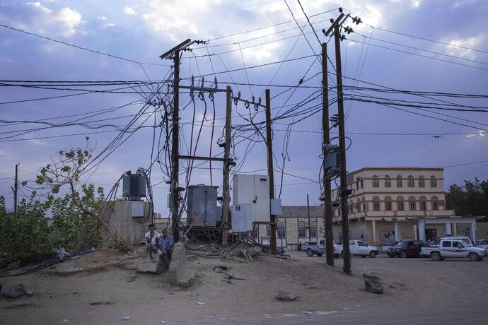 In this July 29, 2019 photo, Ethiopian Oromo migrants sit under electric cables in Al Hosoun area, where they gather to find work, in Marib, Yemen. In the evenings, thousands of migrants mill around the streets of Marib, one of the main city stopovers on the migrants' route through Yemen. In the mornings, they search for day jobs. They could earn about a dollar a day working on nearby farms. A more prized job is with the city garbage collectors, paying $4 a day. (AP Photo/Nariman El-Mofty)