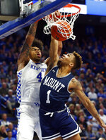 Kentucky's Nick Richards, left, dunks while defended by Mount St. Mary's Dee Barnes (1) during the second half of an NCAA college basketball game in Lexington, Ky., Friday, Nov. 22, 2019. Kentucky won 82-62. (AP Photo/James Crisp)