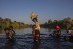 A little girl holds her stuffed animal high above the water as migrants, many from Haiti, wade across the Rio Grande river from Del Rio, Texas, to return to Ciudad Acuña, Mexico, Monday, Sept. 20, 2021, to avoid deportation. The U.S. is flying Haitians camped in a Texas border town back to their homeland and blocking others from crossing the border from Mexico. (AP Photo/Felix Marquez)