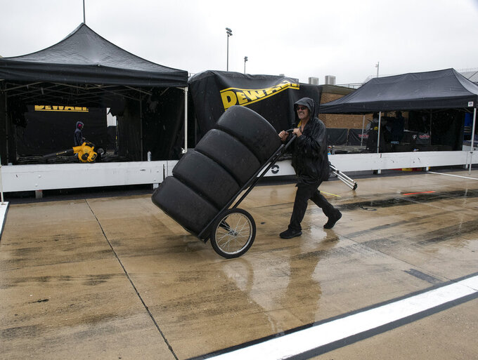 Tires are moved through the pit area as rain falls before a NASCAR Cup series auto race at Dover International Speedway in Dover, Del., Sunday, May 5, 2019. (AP Photo/Jason Minto)