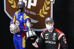 Josef Newgarden holds the trophy after winning an IndyCar auto race at Indianapolis Motor Speedway in Indianapolis, Friday, Oct. 2, 2020. Alexander Rossi, left, finished second. (AP Photo/Michael Conroy)