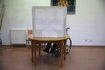 Olivia Bibe, 87, marks her presidential election ballot behind a makeshift voting booth at the elderly care home where she resides in Montijo, south of Lisbon, Tuesday, Jan. 19, 2021. For 48 hours from Tuesday, local council crews are collecting the votes from people in home quarantine and from residents of elderly care homes ahead of Sunday's presidential election. (AP Photo/Armando Franca)