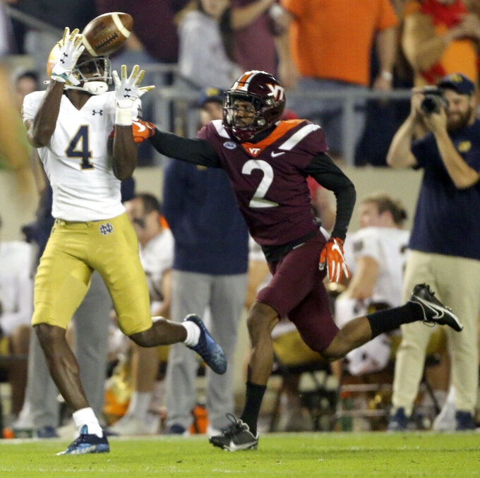 Notre Dame wide receiver Kevin Austin Jr. (4) catches a pass in front of Virginia Tech defensive back Jermaine Waller (2) during the first half of an NCAA college football game in Blacksburg, Va., Saturday, Oct. 9, 2021. (AP Photo/Matt Gentry)