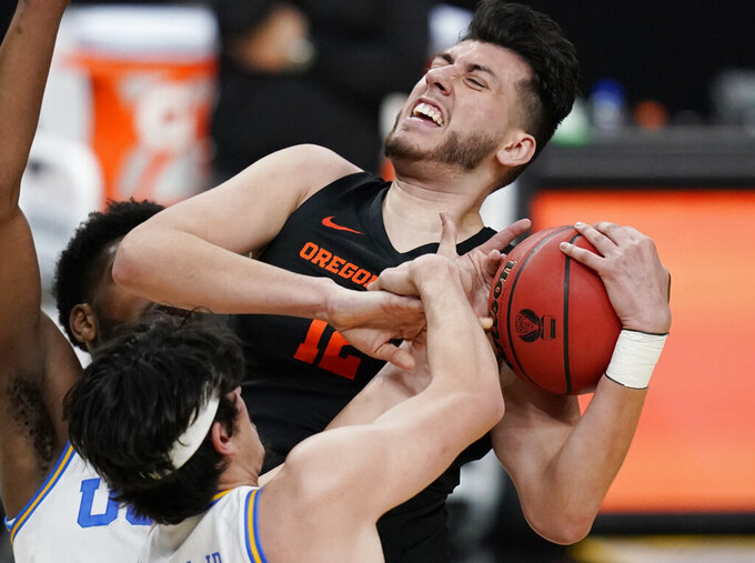 UCLA's Jaime Jaquez Jr. (4) fouls Oregon State's Roman Silva (12) during the first half of an NCAA college basketball game in the quarterfinal round of the Pac-12 men's tournament Thursday, March 11, 2021, in Las Vegas. (AP Photo/John Locher)