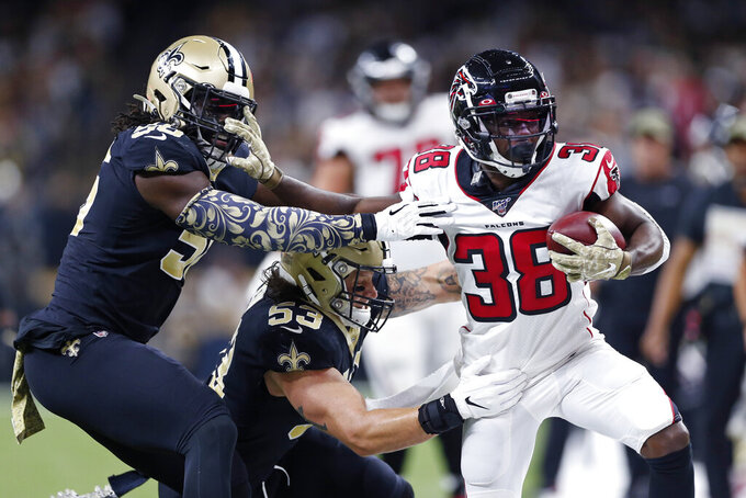Atlanta Falcons running back Kenjon Barner (38) carries against New Orleans Saints outside linebacker Demario Davis and outside linebacker A.J. Klein (53) in the first half of an NFL football game in New Orleans, Sunday, Nov. 10, 2019. (AP Photo/Rusty Costanza)