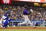 Colorado Rockies' Josh Fuentes, right, hits a solo home run as Los Angeles Dodgers catcher Russell Martin watches during the seventh inning of a baseball game Saturday, Sept. 21, 2019, in Los Angeles. (AP Photo/Mark J. Terrill)