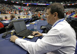 In this photo taken March 9, 2019 Precision Time inventor Mike Costabile, a former referee, keeps track of a log of the system during the second half of an Atlantic Coast Conference women's tournament basketball game in Greensboro, N.C. The Precision Time system created more than two decades ago by Costabile currently is used at nearly every level of the sport, including the NBA and college basketball's NCAA Tournament. Costabile estimates the ability to stop the clock automatically on a referee's whistle can save roughly 90 seconds formerly lost to reaction time when timekeepers manually stopped the clock. (AP Photo/Chuck Burton)