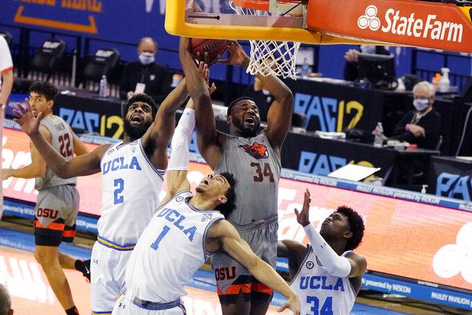 Oregon State forward Rodrigue Andela (34) grabs rebound over UCLA forward Cody Riley (2) and guard Jules Bernard (1) during the first half of an NCAA college basketball game Saturday, Jan. 30, 2021, in Los Angeles. (AP Photo/Marcio Jose Sanchez)
